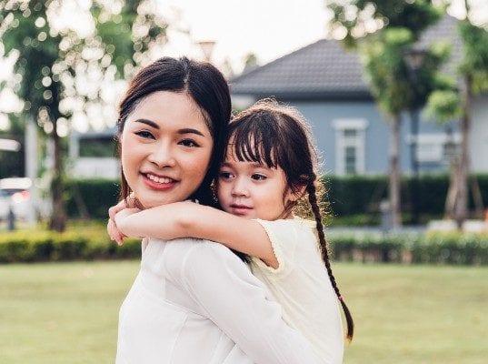 mom-giving-child-piggyback-ride-outside