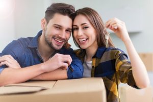 young-smiling-couple-with-house-keys-and-moving-boxes