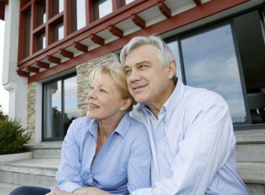 older-couple-sitting-outside-house