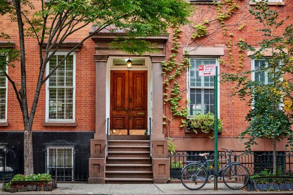 brick-brownstone-with-trees-and-bicycle-on-sidewalk