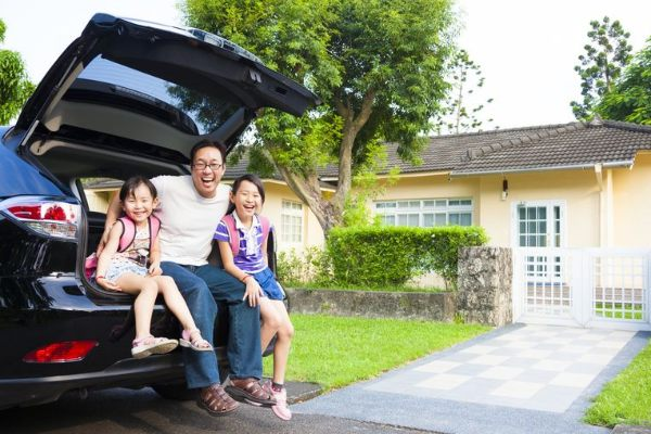 father-and-daughters-sitting-in-back-of-car-outside-house