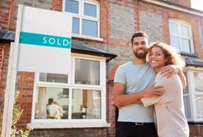 happy-couple-hugging-in-front-of-home-sold-sign