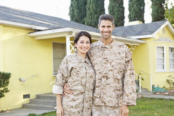 military-couple-outside-yellow-house